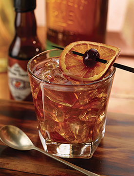 Featuring a twist on the founder Ruth Fertel's favorite drink, the New (Old) Fashioned, garnished by Dress The Drink, featuring a candied orange.