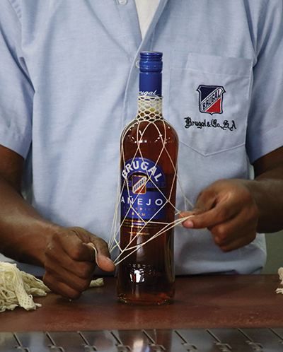 Putting the famous netting on a bottle of Añejo.
