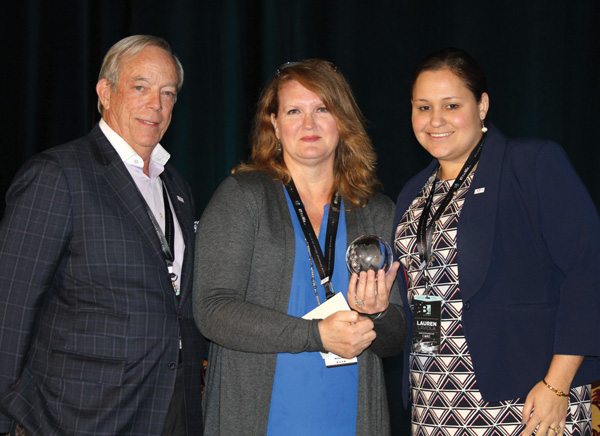 Joe Smith, left and Lauren LaViola, right, present an award to Sherry King, center, CFO of IMI, for her years of charitable work as the accountant for CORE.