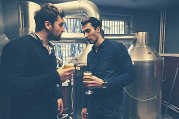 Two Handsome Male Tasting Beer In Brewery