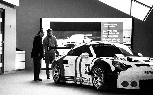 Don Billings and Adam Billings getting a kick out of a Porsche covered in LEGOS®.