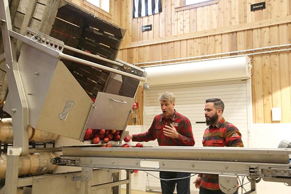 Ryan showing Pete the apple harvesting equipment.