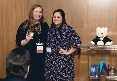 Lindsey Johnson, Founder and CEO of Lush Life Productions, receiving her company's award from Lauren LaViola.